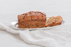 Traditional British fruit loaf on an oval plate on a pale background. Fruit loaf made with dried fruits, two slices cut set on an oval plate with napkin stock photos