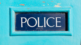 Traditional British Police sign written on dark blue background Royalty Free Stock Photos