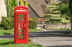 Traditional British red telephone box in a Cotswold village royalty free stock photography