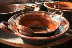 Brown Clay Cooking Pots Stacked up on Wood Table stock image