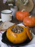 Traditional buckwheat porridge with meat and vegetables baked in pumpkin on wooden background. Autumn dish. Selective stock photo