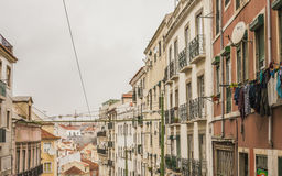 Traditional buildings, Lisbon, Portugal. A view of a street with some traditional old buildings in Lisbon, Portugal. There are some red-tiled roofs and crossing Stock Photo