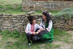 Traditional Bulgarian Folklore. A beautiful young women and a handsome boy in folklore costumes shot in the old village of Leshten, Bulgaria royalty free stock photography