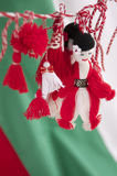 Traditional Bulgarian Martenitsa on National Flag. Martenitsa is a small piece of adornment, made of white and red threads. It symbolizes spring and the wish for Royalty Free Stock Images