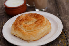 Traditional Bulgarian pastry Banitsa. On a rustic table with Greek yogurt and juice Stock Images