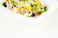 Traditional Bulgarian Shepherd salad with tomatoes, peppers, cucumbers, mushrooms, ham, cheese and eggs in white dish on white woo Stock Photography