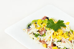 Traditional Bulgarian Shepherd salad with tomatoes, peppers, cucumbers, mushrooms, ham, cheese and eggs in white dish on white woo Stock Image