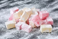 Traditional bulgarian turkish delight lokum, ordinary and rose flavoured, on black board with powederd sugar. Traditional bulgarian turkish delight lokum candies stock images