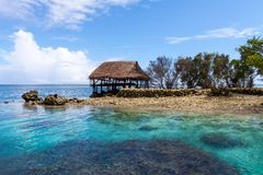 Traditional bungalow of native aborigines Micronesian people. Reef coral island motu. Blue azure turquoise lagoon. Pohnpei island. royalty free stock photography