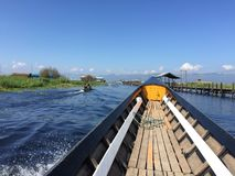 Traditional Burmese boat, sailing. Prow of a traditional Burmese boat sailing by Inle Lake, Myanmar. Paesajistica view of the lake and villages stock image