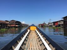 Traditional Burmese boat, sailing. Prow of a traditional Burmese boat sailing by Inle Lake, Myanmar. Paesajistica view of the lake and villages royalty free stock images