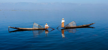 Traditional Burmese fishermen at Inle lake. Panorama of traditional Burmese fishermen with fishing net at Inle lake in Myanmar famous for their distinctive one stock images
