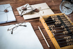 Traditional business concept. Vintage abacus envelopes and alarm clock on wooden table stock images