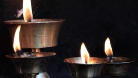 Traditional butter lamps. Placed at a temple in Kathmandu. Butter lamps are a conspicuous feature of Tibetan Buddhist temples and monasteries throughout the stock video