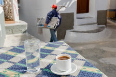 Traditional cafe on a small square in the village of Olympia in Greece. The traditional coffee is always served with a glass of iced water. We drink it stock photo