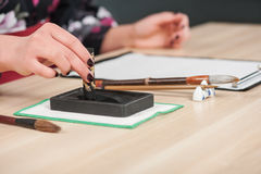 Traditional calligraphy on wooden table Stock Photography