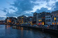 Traditional canal houses on the Damrak at dusk in Amsterdam. stock image