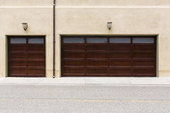 Traditional 3 car garage. 3 car garage with brown door, windows and lamposts Royalty Free Stock Photography