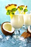 Traditional caribbean cocktail pina colada in a glasses. Traditional caribbean cocktail pina colada in a glasses on a blue slate,stone or concrete background royalty free stock images
