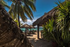 Traditional caribbean mexican beach restaurant with chairs and tables, palapa and palm trees Royalty Free Stock Image