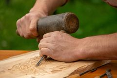Traditional carpenter close up working hands with carpeting tools. Traditional carpenter close up working hands with carpeting tools carving wood royalty free stock images