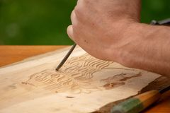 Traditional carpenter close up working hands with carpeting tools. Traditional carpenter close up working hands with carpeting tools carving wood stock photo