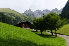 Traditional chalet in the european alps on a green mountain pasture royalty free stock photos
