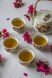 Traditional Japanese tea set filled with green tea and fresh red cheery blossom against white marble back. Traditional cherry blossom decorated Japanese tea set royalty free stock image