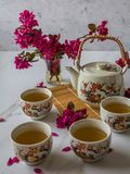 Traditional cherry blossom decorated Japanese tea set filled with green tea and fresh red cheery blossom. Against white marble background. Copy space,  healthy stock photo