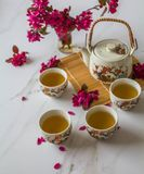 Traditional cherry blossom decorated Japanese tea set filled with green tea and fresh red cheery blossom. Against white marble background. Copy space,  healthy stock photography