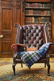 Traditional Chesterfield armchair. With tartan blanket in classical library room Stock Images