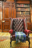Traditional Chesterfield armchair. With tartan blanket in classical library room Royalty Free Stock Image