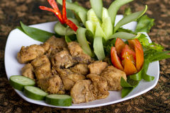 Traditional chicken dishes. Chicken rica-rica is authentic Indonesian cuisine with a strong flavor spices, served on white plate lined with batik tablecloths Stock Photo