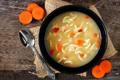Traditional chicken noodle soup, overhead scene on rustic wood Royalty Free Stock Photography