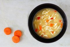 Traditional chicken noodle soup, overhead view on white marble Stock Photography