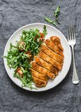Traditional chicken schnitzel with arugula cherry tomatoes salad on grey background stock photos
