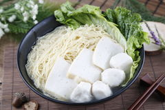 Traditional chinese bowl of wanton vermicelli with fish ball and. Paste on the table in restaurant deliciously Royalty Free Stock Photo