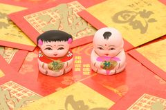 Traditional Chinese boy and girl figurines. On red packets background Stock Photos