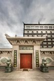 A traditional Chinese building at Dragon Gate. Massive red entrance door with lion statues, hotel building and dark clouds. ALVKARLEBY, SWEDEN - JULY 27, 2014 royalty free stock image