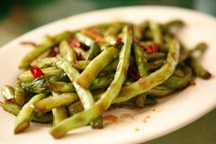 A traditional Chinese dish of green string beans with red chili pepper, served in a white plate. Beijing, China. royalty free stock images