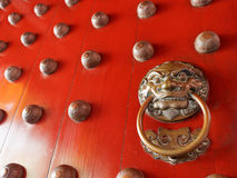 Traditional Chinese doors with brass handles symbolic of lion's heads Royalty Free Stock Photography