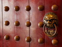 Traditional Chinese doors with brass handles symbolic of lion's heads Stock Images