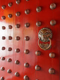 Traditional Chinese doors with brass handles symbolic of lion's heads. It's believe to ward off evil and usher in good luck for the occupants Stock Images