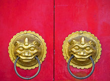 Traditional Chinese doors. With brass handles symbolic of lion's heads. It's believe to ward off evil and usher in good luck for the occupants Royalty Free Stock Photo