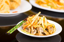 Traditional chinese food, noodles, mushrooms and vegetables on a white dish Royalty Free Stock Image