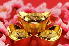 Traditional chinese gold ingots. Front view of some chinese gold ingots surrounded by cherry blossoms on a red background Stock Images
