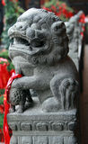 Traditional chinese guardian lion. Male leaning his paw upon an embroidered ball representing supremacy over the world Royalty Free Stock Photo
