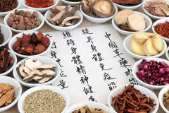Traditional Chinese Herbal Medicine. Chinese herb selection used in herbal medicine with calligraphy script, translation describes chinese herbal medicine as Royalty Free Stock Photo
