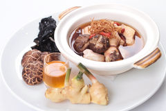 Traditional Chinese herbal soup with chicken and raw ingredients on the side Stock Photo