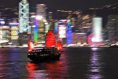Hong Kong Junk Boat Motion Blur. Traditional Chinese junk boat Aqua Luna with red sails on a tour of Victoria Harbour in Hong Kong, China. Iconic night skyline stock photography